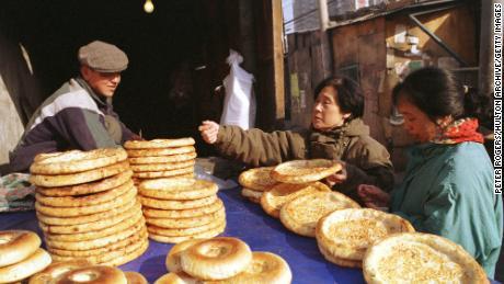 A Uyghur man sells traditional flat bread to women shopping along Beijing's Xinjiang Street in 1999.
