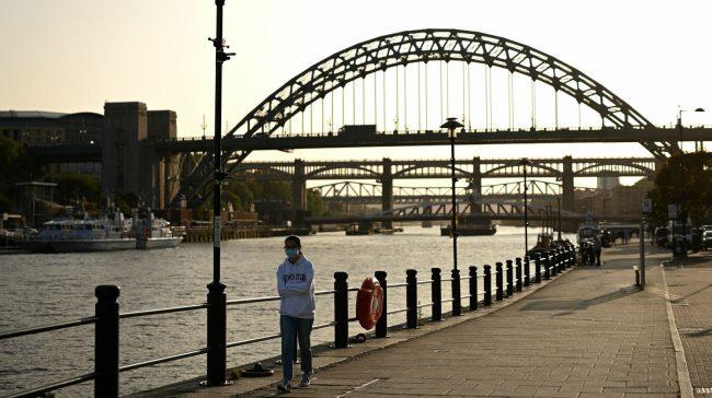 A woman walks near the Tyne Bridge in Newcastle